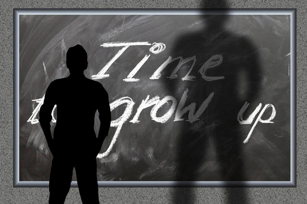Človek pred čiernou tabuľou s nápisom čas rásť